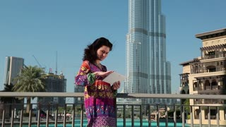 Woman stands near skyscraper and uses tablet computer. Businesswoman with white tablet computer. Adult woman uses tablet computer. Burj Khalifa megatall skyscraper in Dubai, United Arab Emirates