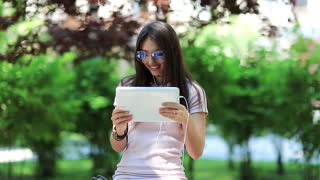 Woman with tablet computer. Beautiful girl uses tablet computer. Attractive girl hold in hands white tablet pc. Woman with tablet pc communicates through videochat