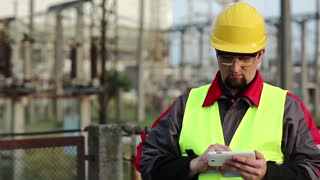 Worker at electric power plant uses smartphone. Power engineering specialist with cell phone in hand on electric power station