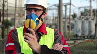 Worker in respirator and with portable radio transmitter on electric power station. Power engineering specialist in gas mask, goggles and hard hat on heat power plant communicates via radio station