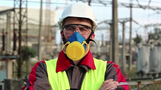 Worker in respirator on electric power station looks at the camera. Power engineering specialist in gas mask, goggles and hard hat at heat power plant