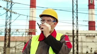 Worker in respirator talks via portable radio transmitter on electric power station. Power engineering specialist in gas mask, goggles and hard hat on heat power plant communicates via radio station