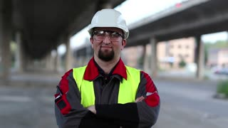 Worker stands under overpass and looks at the camera. Civil engineer in working clothes, white hard hat, goggles at construction site