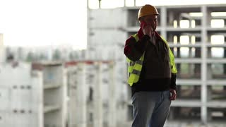 Worker talks on cell phone at construction site. Builder in green vest talks on telephone on project site