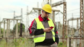 Workman at electric power plant uses smartphone. Power engineering specialist with cell phone in hand on electric power station