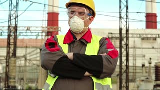 Workman in gas mask speaks via radio transmitter. Power engineering specialist in gas mask, goggles and hard hat on heat power plant communicates via radio station