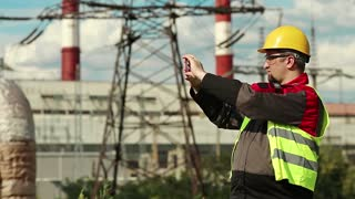 Workman records videos on smartphone. Worker in yellow hard hat with smartphone at electric power plant