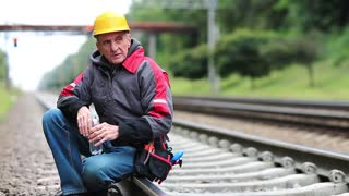Workman sits on branch railway and drinks water from bottle. Railway worker sits on railway line. Repairman in yellow hard hat with tools sits on railway track