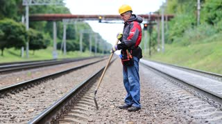 Workman with shovel on railway track. Repairman worker with shovel in hands mends railway line. Railwayman in uniform with shovel in hands repairs railway track. Back hurts, low back pain, lumbago