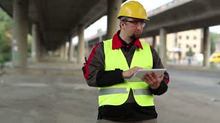 Workman with tablet computer under overpass. Manager of repair works at construction site under overhead road, inputs data in computer