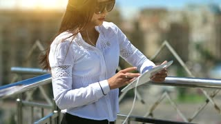 Young attractive girl in sunglasses uses tablet computer. Businesswoman hold in hands tablet computer