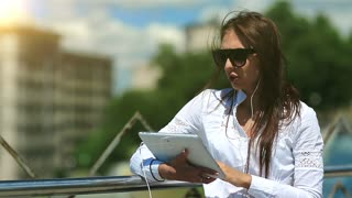 Young attractive girl in sunglasses with tablet computer in hands communicates through skype. Businesswoman communicates via tablet computer