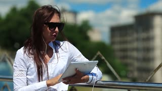 Young attractive girl in sunglasses with tablet computer in hands communicates through skype or video chat. Businesswoman communicates via tablet computer