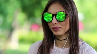 Young beautiful woman in green sunglasses looks at the camera smiles and laugh. Attractive girl with earphones listens to music looks at the camera and smiles