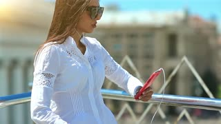 Young beautiful woman listens to music and sings a song. Pretty girl with long hair in sunglasses with red smartphone listens to music in the city