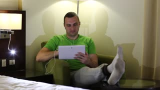 Young man with tablet pc with earpieces sits in armchair in hotel room. Man sits in armchair and uses tablet computer