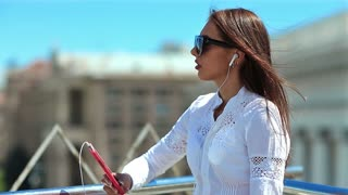 Young woman listens to music and sings a song. Pretty girl with long hair in sunglasses with red smartphone listens to music in the city