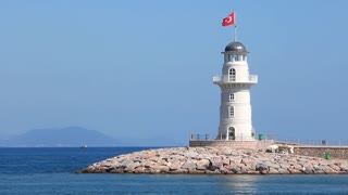 White lighthouse with red national flag of Turkey