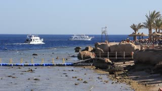White pleasure boats in Red Sea and people on the beach in Sharm El Sheikh, Egypt