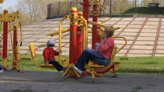 Woman and little boy on gym apparatus