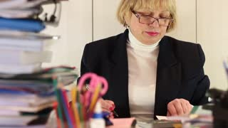 Woman bookkeeper in glasses and with commercial papers sits at the table, calculate and write down. Female with calculator and pen. Businesswoman sits at the table in office among commercial papers