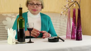 Woman drinking wine and smoking a cigarette. Depressed senior woman with a bottle of wine and cigarette sits at the table
