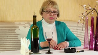 Woman drinking wine and smoking a cigarette. Depressed woman with a bottle of wine and cigarettes sitting at the table