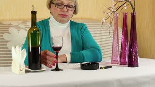 Woman drinks wine and smokes a cigarette. Blonde senior woman with a bottle of wine and cigarette sits at the table. Female with cigarette and glass of wine