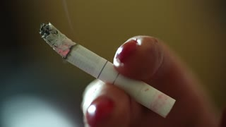 Woman fingers with cigarette, female smoker, extreme close up shot