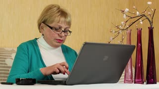 Woman in glasses types text using laptop and smoking a cigarette