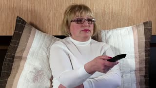 Woman in glasses with remote control sits on the bed and switching tv channels