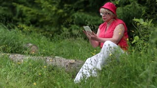 Woman in red cap sits on a fallen tree in the forest and uses smartphone