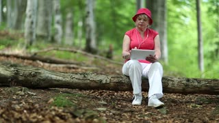 Woman in red cap sits on a fallen tree in the forest and uses tablet PC. Female with tablet computer. Businesswoman with Tablet PC
