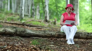Woman in red cap sits on a fallen tree in the forest and uses tablet PC