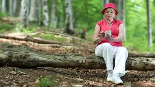 Woman in red cap sits on a fallen tree in the forest and uses white smartphone