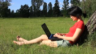 Woman in red t-shirt with notebook on the nature