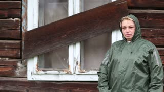 Woman in waterproof raincoat stands near the boarded-up uninhabited house and looks at the camera