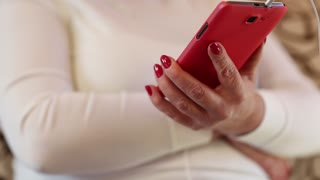 Woman looks and flips through the photos in her smartphone. Female with smartphone. Close up of woman hands with red smartphone. Businesswoman with red mobile phone with earphones