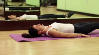 Woman lying on the mat and pumps abdominal muscles. Woman trains in gym. Woman lies on the mat and pumps press. The woman goes in for sports. Physical activity helps burn up calories