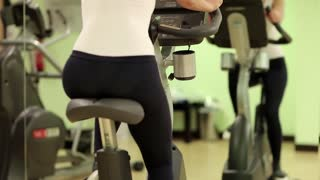 Woman on exercise bicycle in front of a mirror. Woman turns bicycle pedals. Woman sits on an exercise bike and turns pedals. The woman goes in for sports. Woman trains in gym
