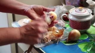 Woman peels the onions