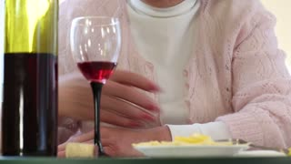 Woman pours and drinks red wine. Depressed senior woman with a bottle of wine sits at the table