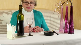 Woman pours and drinks red wine. Senior woman sits at a table and drinks red wine. Female drinking wine