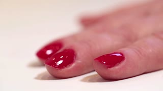 Woman red nails. Manicure procedure with nail sciccors in beauty salon, pare finger-nails