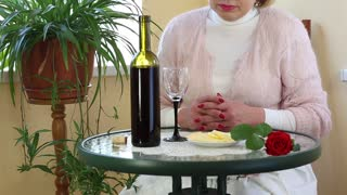 Woman sits at a table and drinks red wine. Senior woman sits at a table, drinks red wine and eats cheese