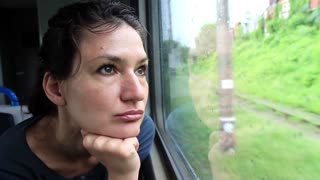 Woman sits in train near window during movement