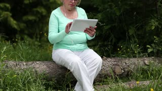 Woman sits on a fallen tree in the forest and uses tablet computer