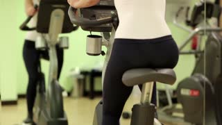 Woman sits on an exercise bike and turns pedals. Woman on exercise bicycle in front of a mirror. Woman turns bicycle pedals. The woman goes in for sports. Woman trains in gym