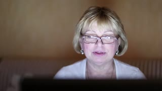 Woman sits on the sofa in a dark room and communicates via laptop. Senior woman with notebook inside dark room. Cheerful woman talking on Skype