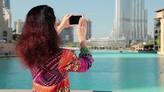 Woman stands near blue pool and makes photos on smartphone. Female makes photos on smartphone. Businesswoman with smartphone. Adult woman uses smartphone near Burj Khalifa megatall skyscraper in Dubai